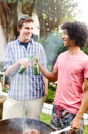 beer garden: Two men with beers toasting in front of a barbeque