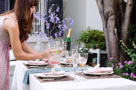 hôtesse: H�tesse apportant cruche d'eau � l'ensemble de table pour une garden-party