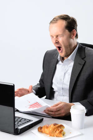 Tired yawning exhausted businessman working tirelessly at his desk, rushing a deadline photo