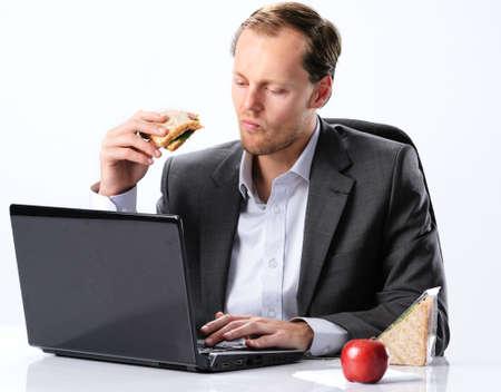 man eten: Drukke zakenman in het kantoor van kleding eten van een boterham aan zijn bureau, werken via zijn lunchpauze uur Stockfoto