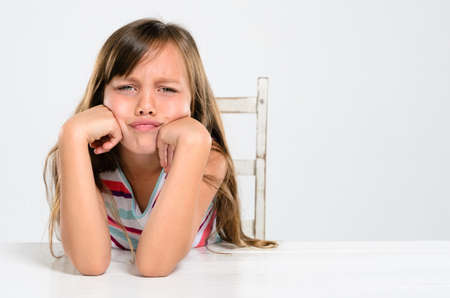 Portrait of young preschool girl pouting and throwing a tantrum at a table photo