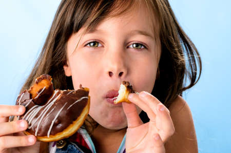 Cute young caucasian girl caught eating a chocolate doughnut photo