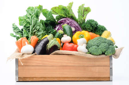 Crate of raw fresh vegetables from the farmers market, assortment of corn, peppers, broccoli, mushrooms, beets, cabbage, parsley, tomatoes, isolated on light background photo