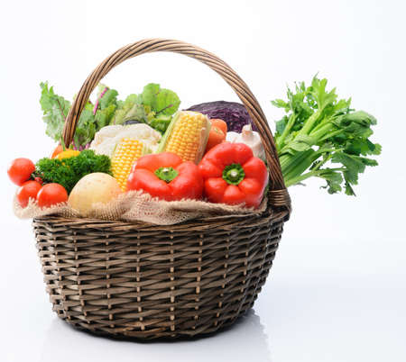shopping basket: Basket of fresh raw organic vegetable produce, assortment of corn, peppers, broccoli, mushrooms, beets, cabbage, parsley, tomatoes, isolated on light background