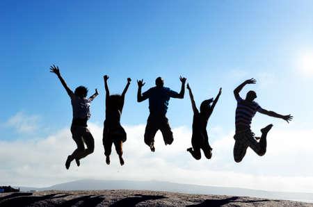 glädje: Silhuetter av grupp vänner hoppa utomhus på en strand i samklang med armarna upp Stockfoto