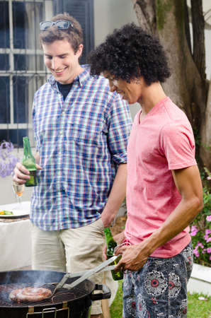 beer garden: Two men having beers by the barbeque at a party, with meat on the smoking grill Stock Photo
