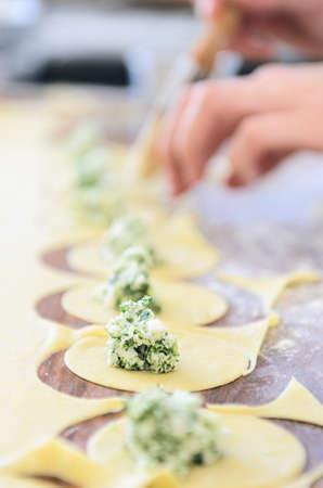 opvulmateriaal: Paar handen vullen tortellini of ravioli met ricotta en spinazie kruid vulling