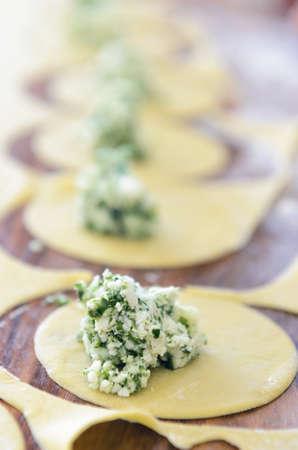 opvulmateriaal: Close-up van verse ravioli vulling spinazie en ricotta op houten ondergrond, met anderen onscherp Stockfoto