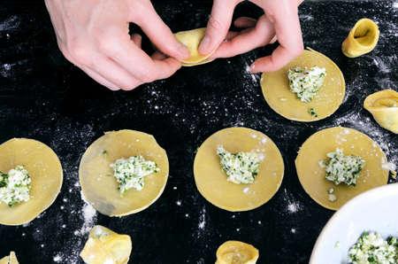 opvulmateriaal: Paar handen vullen tortellini of ravioli met ricotta en spinazie kruid vulling, vanuit bovenaanzicht Stockfoto