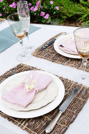 Table setting with napkin and rustic trimmings in the garden photo
