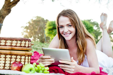 Woman lying on picnic blanket in the park with her tablet computer, wirelessly connected when out in nature Stock Photo - 20309873