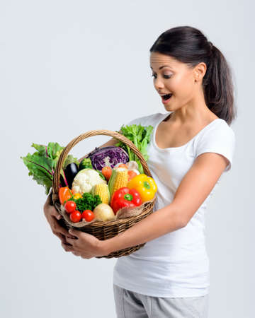 Beautiful mix race woman holding a basket full of fresh organic vegetables with surprised expression  photo