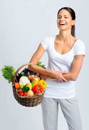 Beautiful woman laughing and holding a basket full of fresh organic vegetables  photo