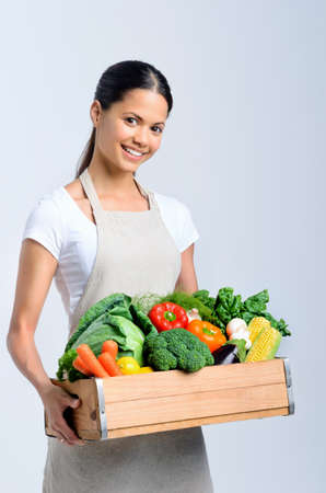 Homemaker chef holding a wooden crate full of fresh raw organic produce vegetables  Stock Photo - 20309863