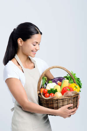 Home chef holds a basket of freshly picked vegetables from her home garden  photo