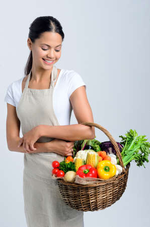 farmers market: Beautiful mix race woman holding and looking to basket full of raw organic vegetables