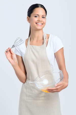 Pretty woman chef holding a whisk and glass bowl with eggs Stock Photo - 20366072
