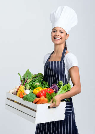 Professional chef holding a crate full of fresh vegetables  photo