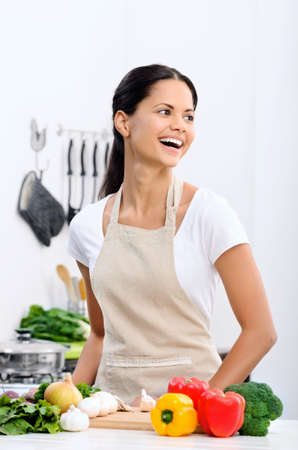 Happy mix race woman cooking and preparing food in the kitchen wearing a apron  Stock Photo - 20309846