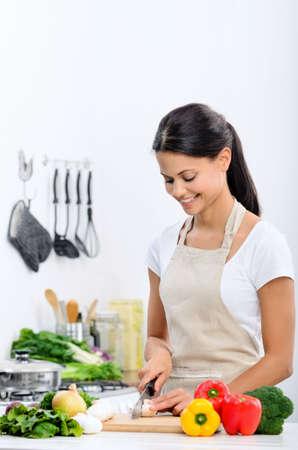 jasschort: Vrolijke mix ras vrouw koken en bereiden van voedsel in de keuken het dragen van een schort