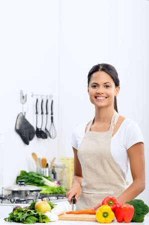 Happy asian woman cooking, slicing and preparing food in the kitchen wearing a apron