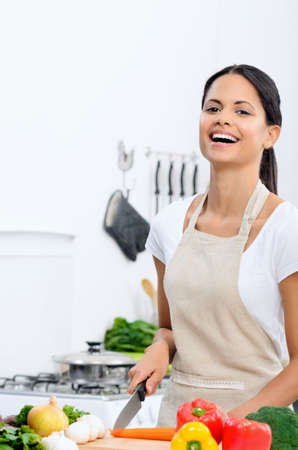 Happy mix race woman laughing while cooking and preparing food in the kitchen wearing a apron  Stock Photo - 20309829