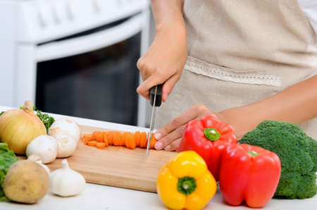 meal preparation: Close up of hands slicing and chopping raw vegetables as meal preparation in a kitchen
