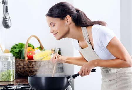 smell: Mujer de pie junto a la estufa de la cocina, cocinando y oliendo los aromas agradables de su comida en una olla