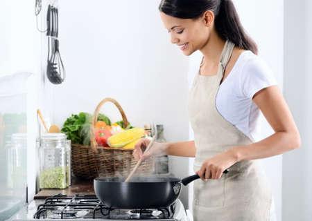 mujeres cocinando: Mujer de pie junto a la estufa de la cocina, cocinando y oliendo los aromas agradables de su comida en una olla