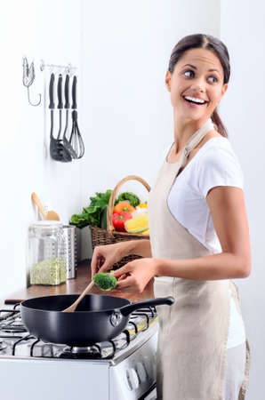 asian cooking: Woman standing by the stove in the kitchen, looking over her shoulder while she stirs and cook