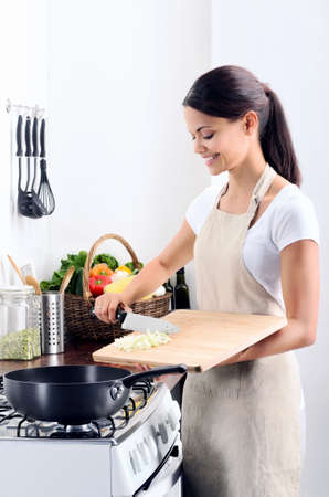 Woman standing by the stove in the kitchen, cooking and adding raw ingredients into the pot photo