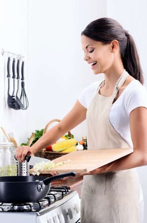 Woman standing by the stove in the kitchen, cooking and adding raw ingredients into the pot Stock Photo - 20309853