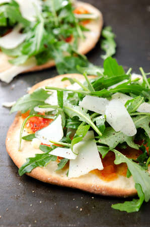 mini oven: Healthy mini pizzas with fresh rocket and shaved parmesan cheese