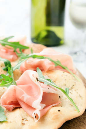 mini oven: Pizza with proscuitto and wild rocket with glass of white wine, gourmet dinner