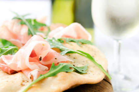 mini oven: Pizza with parma ham and wild rocket with glass of white wine, gourmet dinner