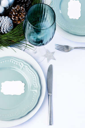 pine cone: Christmas dinner table setting descoration with blue and white theme, plates cutlery and wine glass with pine cone centerpiece