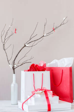 Shopping bags and present gift boxes on table top with elegant interior decoration photo