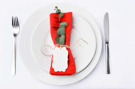 Christmas dinner place setting with red napkin tied with twine holding a place card, deocrated with festive holiday greenery photo