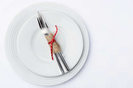 Holiday table setting with cutlery tied in hessian and red ribbon on white table cloth Stock Photo - 20480904