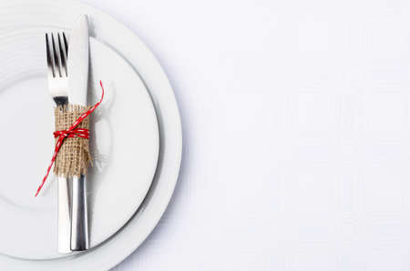 table setting: Holiday table setting with cutlery tied in hessian and red ribbon on white table cloth