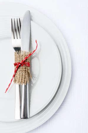헤센 및 빨간 리본 활, 단순 소박한 우아한 테이블 장식으로 묶여 흰색 번호판 그릇과은 칼 저녁 식사 설정 스톡 사진