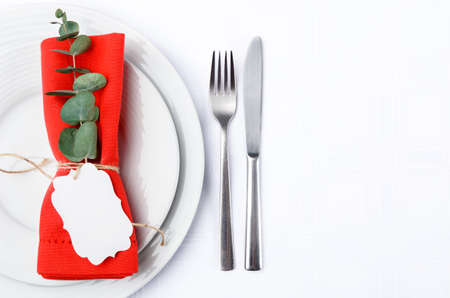 Christmas dinner place setting with red napkin tied with rustic twine holding a place card, deocrated with festive holiday greenery photo