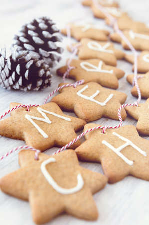 Gingerbread stars with letters spelling 'merry christmas' tied with bakers twine used for christmas decoration and ornament photo