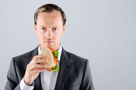 Busy businessman on the move, eating lunch a take away sandwich roll along the way  photo
