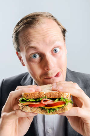 Funny humourous man eating a sandwich with exagerrated wide eye comical expression and sticking his tongue out photo