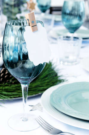 Christmas table setting in blue white and green theme with empty place card photo