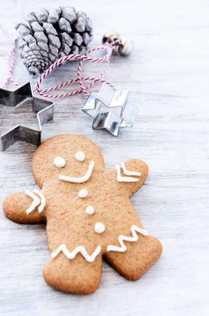 Christmas gingerbread man with pine cones and cookie cutters for festive seasonal holiday background photo