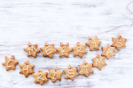 Gingerbread stars with 'merry christmas' tied with bakers twine, white rustic background Stock Photo - 20668758