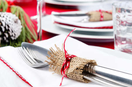 Festive holiday dinner setting, white napkins, crockery, cutlery tied with hessian ribbon detail Stock Photo - 20668766