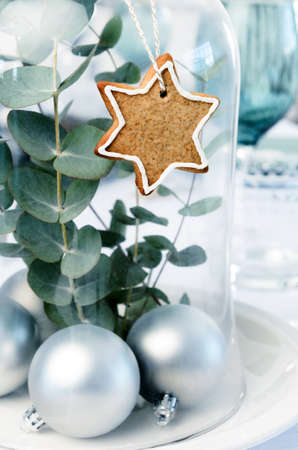 Christmas centerpiece of silver baubles, green leaves in a glass dome decorated with gingerbread star, home DIY for the festive season photo